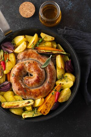 Sausages with potatoes, zucchini, carrots and thyme in a grill pan.