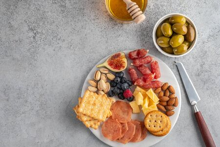 Meat and cheese plate.Traditional italian antipasto, cutting board with salami, cold smoked meat, prosciutto, ham, cheeses, olives, capers on white background. Cheese and meat appetizer. Foto de archivo