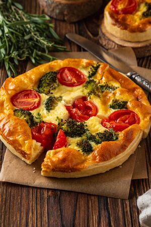 Vegetable pie with broccoli, peas, tomatoes and cheese on wooden background