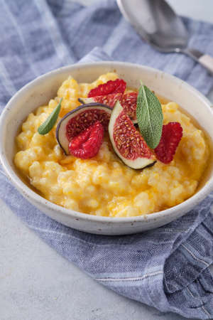 Pumpkin porridge with rice, raspberries and fresh figs. Autumn food. Banco de Imagens
