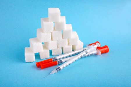 Three insulin syringes and lump sugar on a blue background. World Diabetes Day, November 14. Diabetes concept.