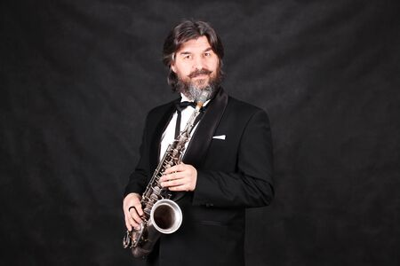 A male artist musician in a classic black suit, tailcoat, statuesque in a bow tie with a beard plays music on a gold saxophone.black background
