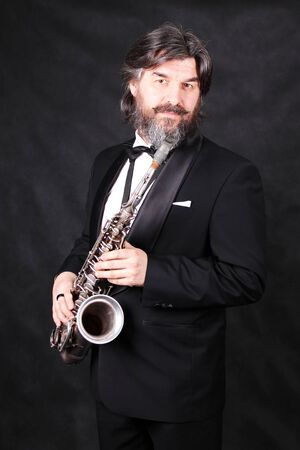 A male artist musician in a classic black suit, tailcoat, statuesque in a bow tie with a beard plays music on a gold saxophone.black background Banque d'images