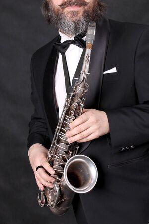 Un musicien artiste masculin dans un costume noir classique, queue de pie, sculptural dans un nœud papillon avec une barbe joue de la musique sur un saxophone doré.fond noir Banque d'images