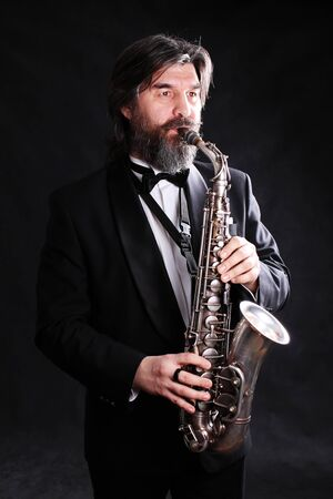 A male artist musician in a classic black suit, tailcoat, stately in a bow tie with a beard plays music on a gold saxophone.black background