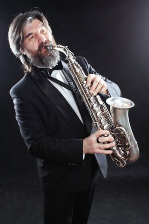 A male artist musician in a classic black suit, tailcoat, statuesque in a bow tie with a beard plays music on a gold saxophone.Playing an instrument against a white light source.black background