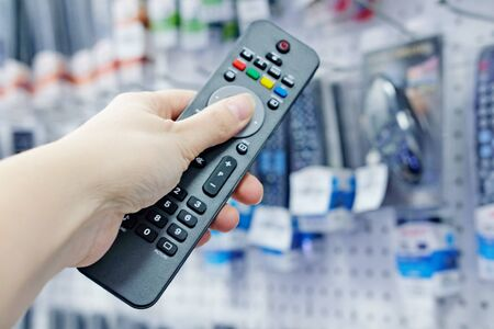 a person's hand presses the control buttons of the TV's black remote control at their leisure with a finger to change the LCD video channel. Selecting and purchasing a remote control in the sto Banco de Imagens