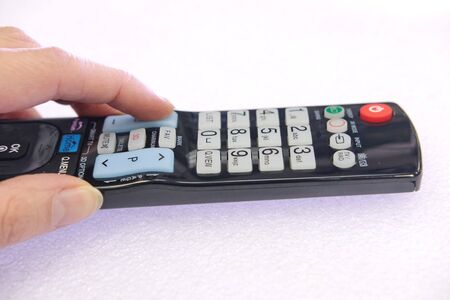 a person's hand presses the control buttons of the TV black remote at their leisure with their finger to change the lcd video channel