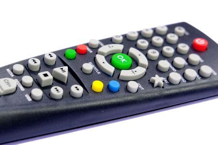 one black, dark gray TV remote control channel switch, green OK button, on a light, white background with backlight