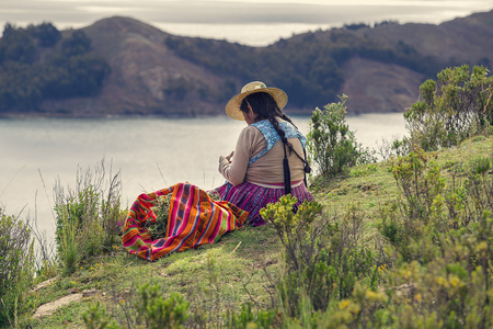 Travel to Bolivia: woman in traditional costume near Titicaca lake