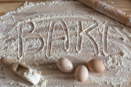 Bakery background. Flour artwork with food eggs, wooden spoon with flour and wooden rolling pin, fun background with the word Bake, and in scattered flour on a wooden tabletop Фото со стока