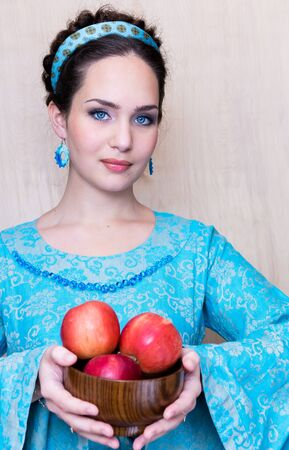a girl in a traditional blue dress with apples. Stock Photo