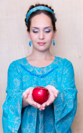 unfocused girl in a blue dress with Apple in the Palm of your hand.