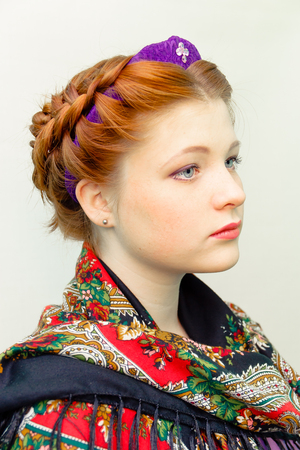 girl with a hair style in a Slavic style and in a color scarf.