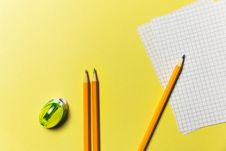 Sharpener, list for recording, pencils on a yellow background Office theme. Фото со стока - 94321597