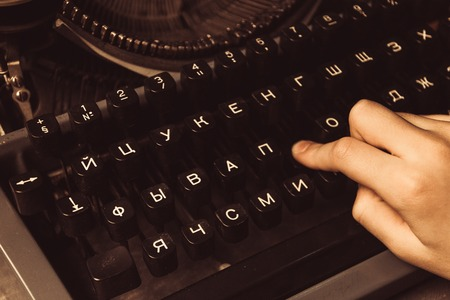 hand on a typewriter on a wooden background. Stock Photo
