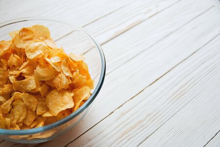 chips in a glass cup on a white wooden backdrop, harmful food.