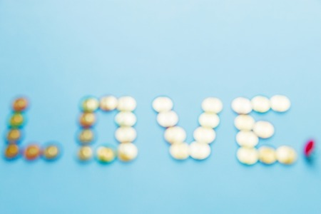 blured word love from pins collection of stationery multicolored buttons, love theme.