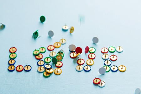 Broken word love from pins collection of stationery multicolored buttons, love theme.