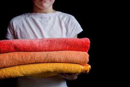 a girl holds towels in their hands, on black background