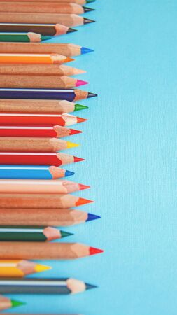 colored pencils on blue background, vertical image Stock Photo