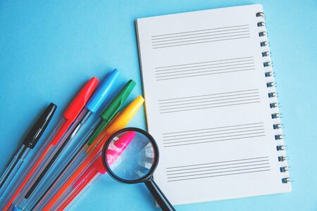 colored pens and magnifier on a white sheet of notepad for text. Stock Photo