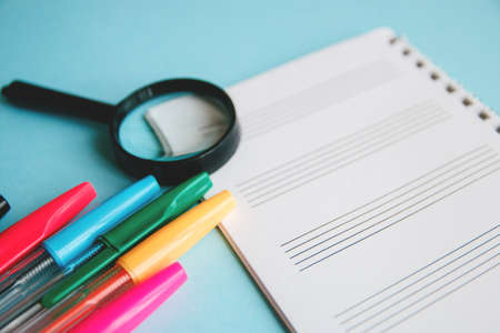 colored pens and magnifier on a white sheet of notepad for text. Education or business concept.