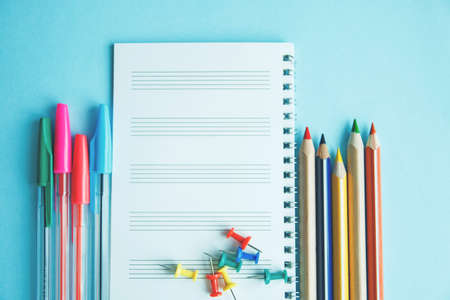 Different school or office supplies on a blue background. Education or business concept. Empty place for text