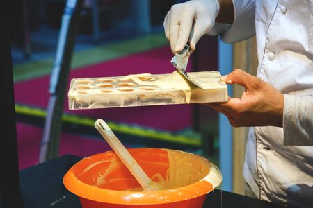 pastry chef fills molds with dough.