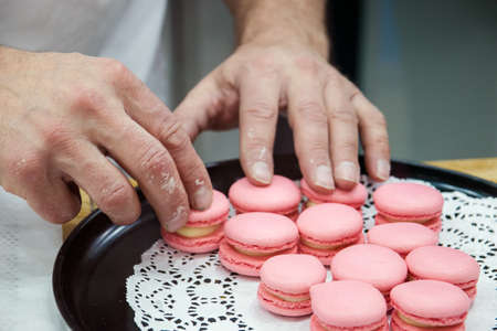 chef with macaroons on tray at bakery. Stock Photo