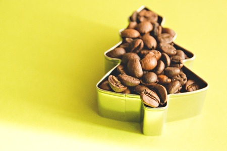 spruce from the coffee beans in a metal mold on a yellow background.
