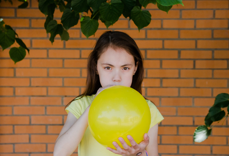 girl inflates the yellow ball.