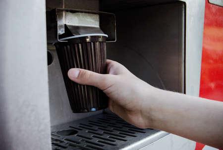 Close-up van de hand neemt een glas water uit het apparaat met water. Stockfoto