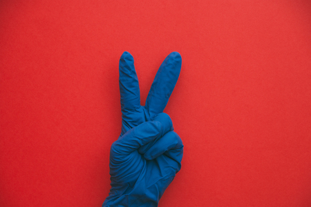 insulated hand in blue glove hand gesture as two or peace sign. Stock Photo