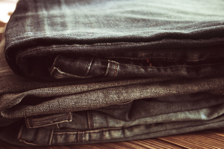 stack of jeans on wooden background, toning vintage image.