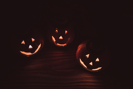 three glowing pumpkin faces for Halloween on wooden background. the symbol of Halloween. Stock Photo