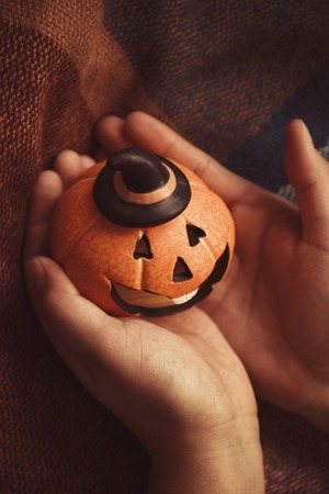 laughing pumpkin for Halloween on a warm cozy blanket in female hands Halloween symbol. Stock Photo
