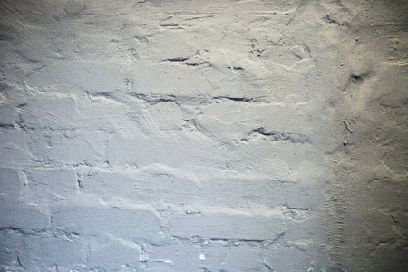 gray uneven textured brick wall background texture.