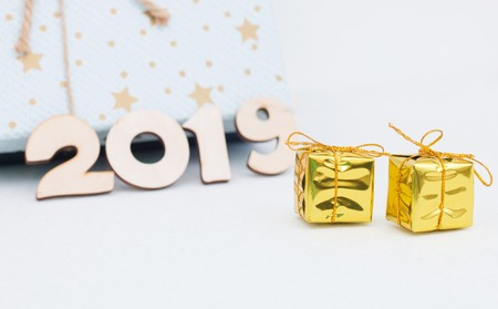 gold gift boxes and symbol numbers 2019 new year on white background, simple flatlay card of new year