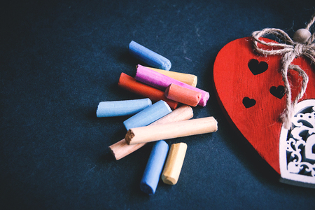 handmade red heart close-up and pieces of pastel chalks on dark background, symbol of love, happy Valentines day.