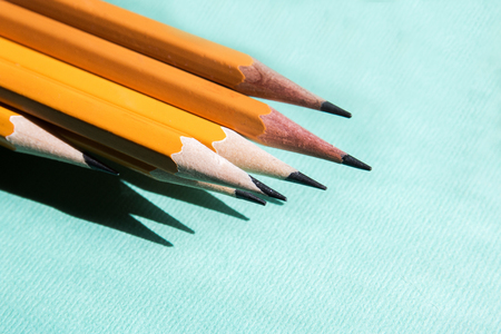 five simple pencils blue background with copy space
