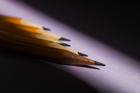 five simple pencils on a solid purple background in hard sunlight contrasting light from the window with a copy space.