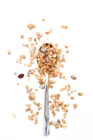 Crunchy muesli on a spoon Breakfast cereals isolated on a white background, selective focus, top view.