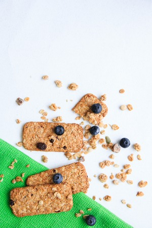 Crunchy muesli cookies and blueberries on green napkin, Breakfast cereals isolated on white background, selective focus, top view.