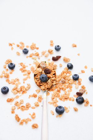 Crispy muesli and blueberry on a spoon Breakfast cereal isolated on white background, selective focus, top view. Archivio Fotografico - 122115382