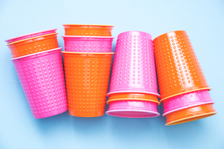 colored plastic cups stacks pink orange on blue background selective focus.