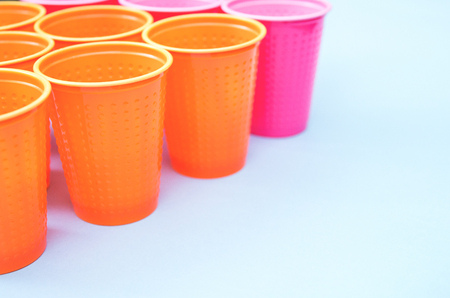 colored plastic cups pink orange on blue background selective focus. 写真素材 - 122119923