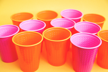 colored plastic cups pink orange on yellow background selective focus. 写真素材 - 122119924