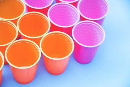 colored plastic cups pink orange on blue background selective focus. 写真素材