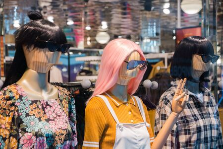 mannequins with modern clothes in fashion store display window. Stockfoto